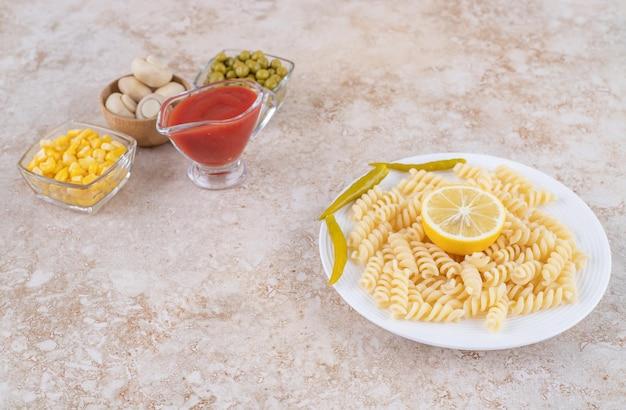 Mały pojemnik na keczup i składniki sałatki obok dania głównego wystawione na marmurowej powierzchni.