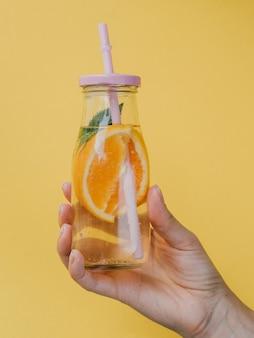 Mały pojemnik na naturalny sok ze słomką w ręku