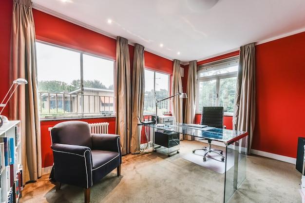 Mały pokój biurowy z czerwonymi ścianami i kilkoma meblami