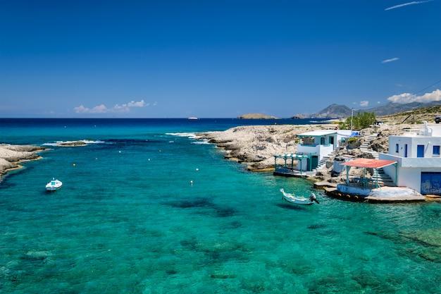 Mały port z łodziami rybackimi w czystej wodzie, bielony dom. wieś mitakas, wyspa milos, grecja.