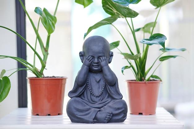 Mały posąg buddy z roślinami w tle