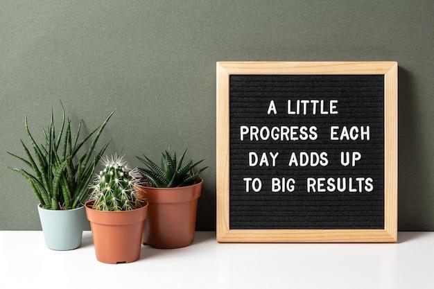Mały postęp każdego dnia to duże efekty. cytat motywacyjny na tablicy z kaktusami