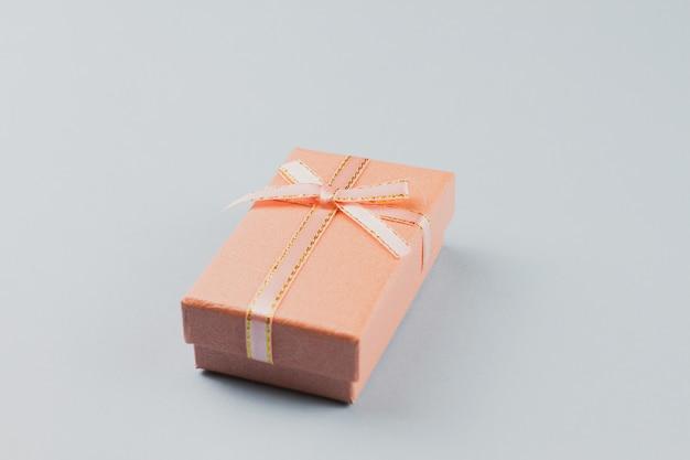 Mały prezent na pastelowej ścianie, zbliżenie. pudełko z kokardą