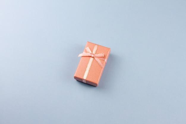 Mały prezent na pastelowym stole, zbliżenie. pudełko z kokardą.