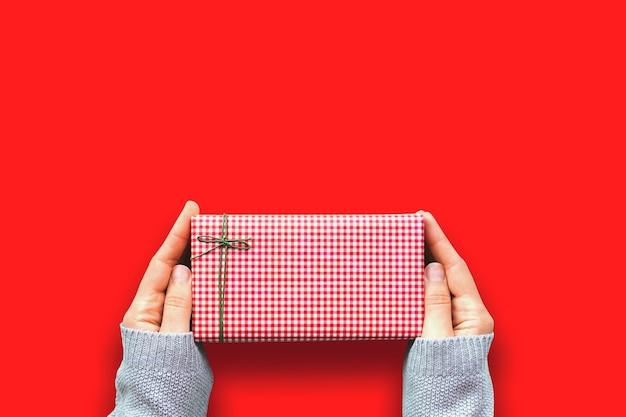 Mały prezent w czerwonym pudełku w rękach kobiety w przytulnym szarym swetrze. papier ozdobny ozdobiony zieloną kokardką na czerwonym tle świątecznym. widok z góry. skopiuj miejsce na górze.
