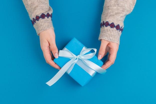 Mały prezenta pudełko w kobiet rękach na błękitnym tle, widok od above