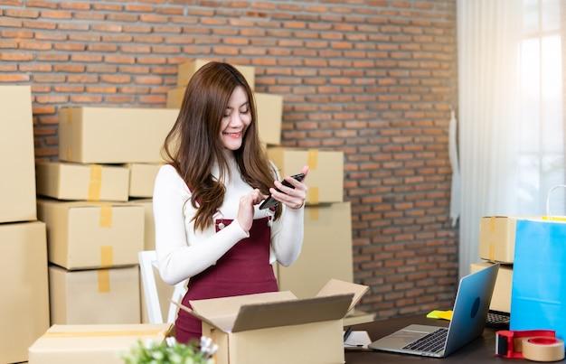 Mały przedsiębiorca rozpoczynający działalność jako mśp lub niezależna kobieta pracująca z pudełkami w domu lub biurze. obsługa paczek dostawczych