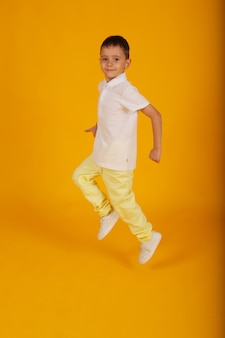 Mały przystojny chłopak w żółtych spodniach i białej koszulce na żółtym tle