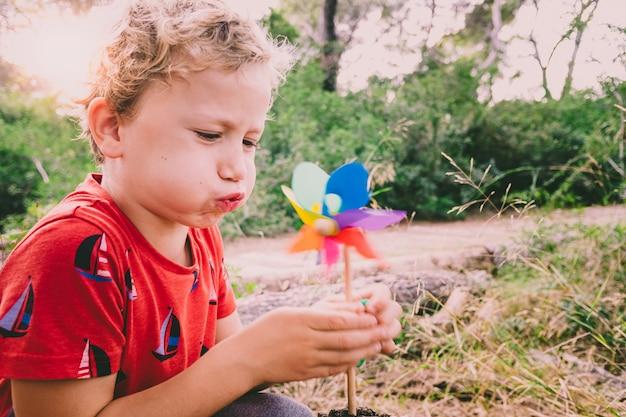 Mały przystojny chłopak wieje wiatraczek w lesie, beztroski, z wyblakłymi tonami i stylem retro.