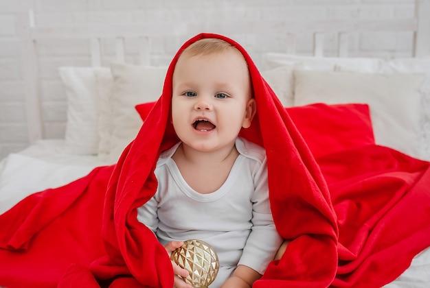 Mały przystojny chłopiec w białym body siedzi na łóżku z czerwonym kocem