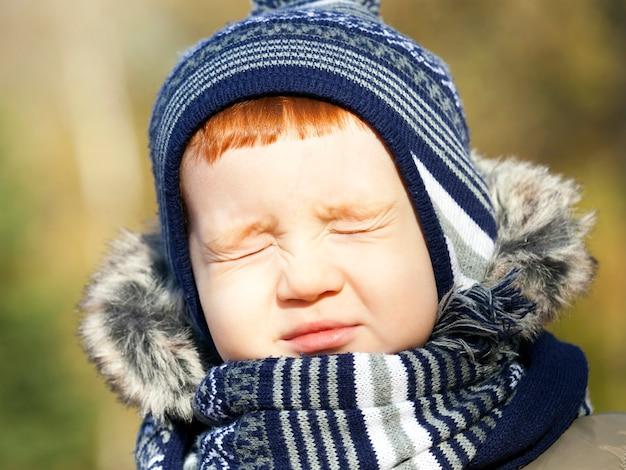 Mały przystojny chłopiec z zamkniętymi oczami w jesiennym parku, zdjęcie z bliska, dziecko ma rudy kolor włosów