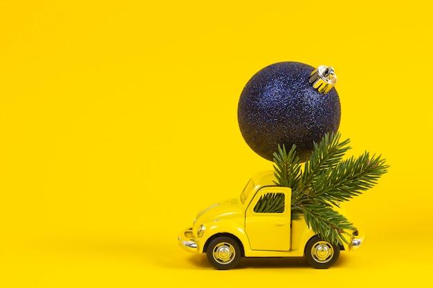 Mały retro zabawkowy model samochodu z dekoracją świąteczną na żółto