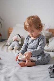 Mały roczek bawi się na łóżku ze swoimi ulubionymi zabawkami zdjęcie ze stylu życia
