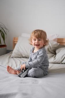 Mały roczek chłopiec bawi się na łóżku ze starym aparatem, zdjęcie stylu życia