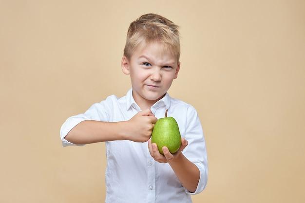 Mały, rozczochrany mrużąc oczy, bije zieloną gruszkę