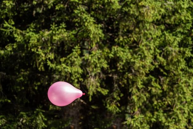 Mały różowy ballon latanie w niebie z las zieleni tłem
