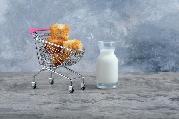 Mały różowy wózek smacznych ciasteczek ze szklanym dzbankiem mleka na marmurowym stole.