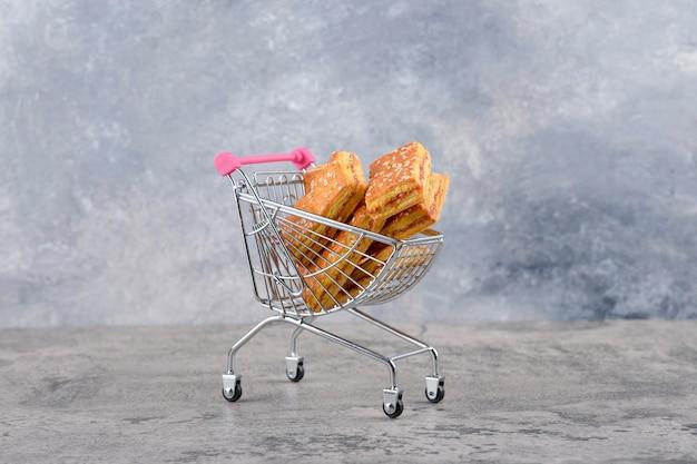 Mały różowy wózek ze smacznymi ciasteczkami na marmurowym stole.
