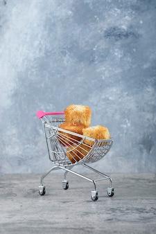 Mały różowy wózek ze smacznymi ciasteczkami ustawiony na marmurowym stole.