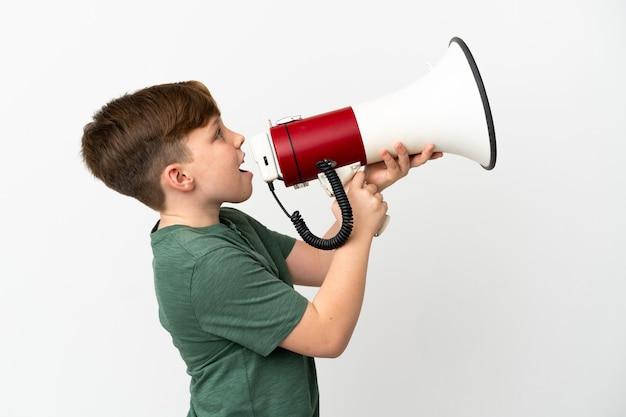 Mały rudy chłopiec na białym tle krzyczy przez megafon, aby ogłosić coś w pozycji bocznej
