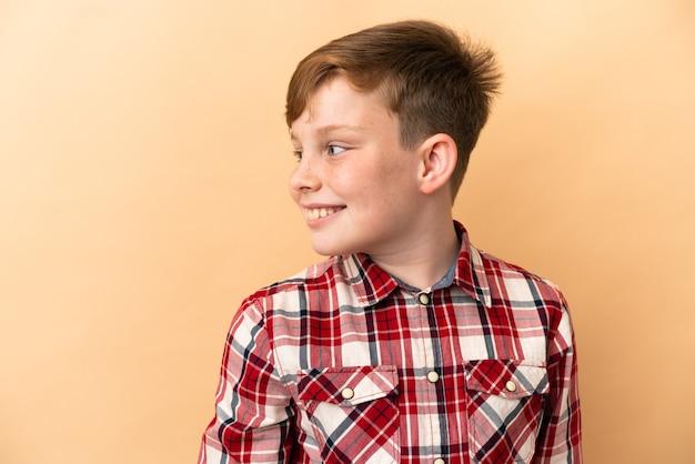 Mały rudy chłopiec na białym tle na beżowym tle