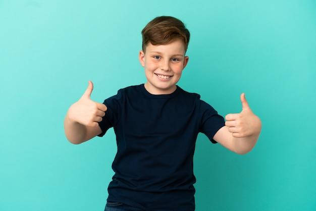Mały rudy chłopiec na białym tle na niebieskim tle dający gest kciuka w górę