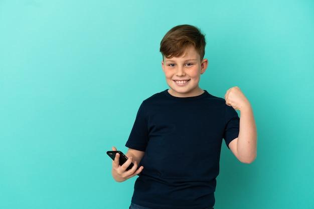 Mały rudy chłopiec na białym tle na niebieskim tle z telefonem w pozycji zwycięstwa