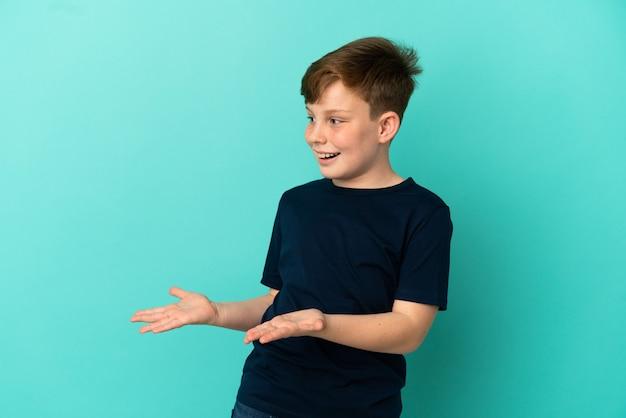 Mały rudy chłopiec na białym tle na niebieskim tle z wyrazem zaskoczenia, patrząc z boku