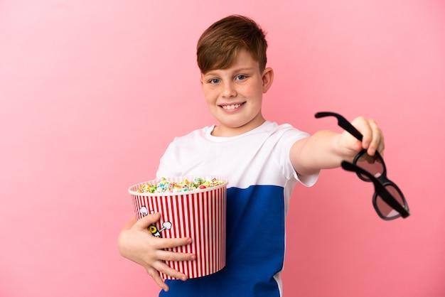 Mały rudy chłopiec na białym tle na różowym tle w okularach 3d i trzymający duże wiadro popcornów