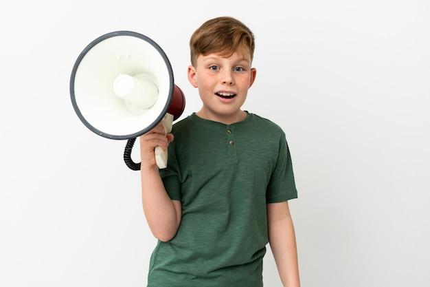 Mały rudy chłopiec na białym tle trzymający megafon i z wyrazem zaskoczenia