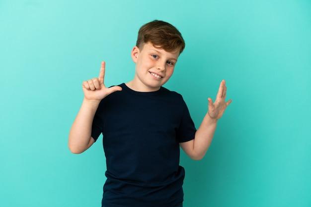 Mały rudy chłopiec na niebieskim tle, licząc siedem palcami