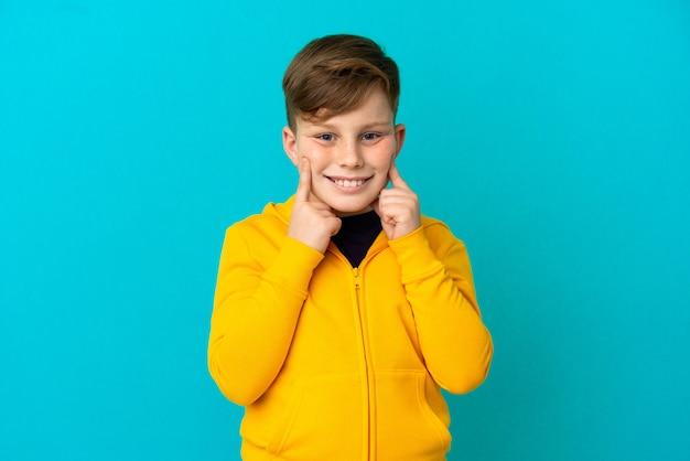 Mały rudy chłopiec na niebieskim tle uśmiechający się ze szczęśliwym i przyjemnym wyrazem twarzy