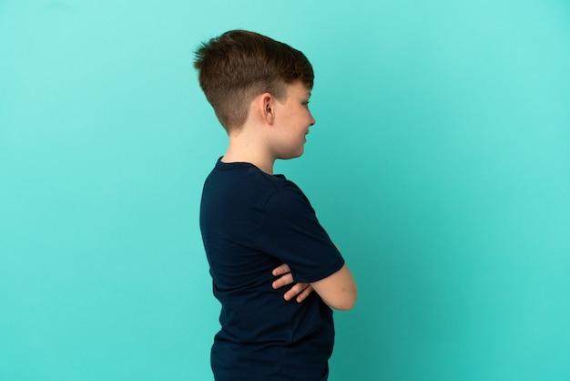 Mały rudy chłopiec na niebieskim tle w pozycji bocznej
