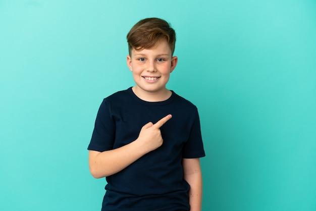 Mały rudy chłopiec na niebieskim tle wskazujący na bok, aby zaprezentować produkt