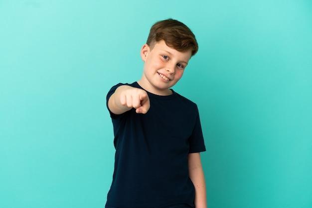 Mały rudy chłopiec na niebieskim tle wskazujący przód ze szczęśliwym wyrazem twarzy