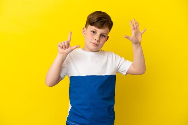 Mały rudy chłopiec na żółtym tle, licząc siedem palcami