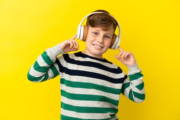 Mały rudy chłopiec na żółtym tle słuchając muzyki i śpiewając