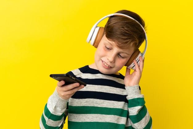 Mały rudy chłopiec na żółtym tle słuchający muzyki za pomocą telefonu komórkowego i śpiewania
