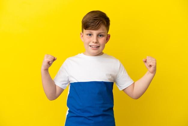 Mały rudy chłopiec na żółtym tle świętuje zwycięstwo w pozycji zwycięzcy