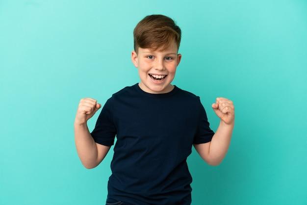 Mały rudy chłopiec odizolowany na niebieskim tle świętujący zwycięstwo w pozycji zwycięzcy