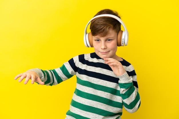 Mały rudy chłopiec odizolowany na żółtej powierzchni słuchając muzyki i tańcząc