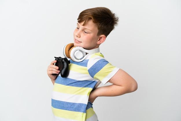 Mały rudy chłopiec trzymający konsolę do gier na białym tle cierpiący na ból pleców za wysiłek
