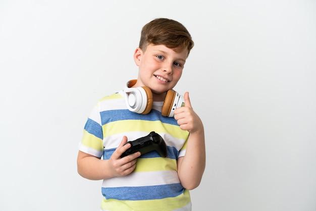 Mały rudy chłopiec trzymający konsolę do gier na białym tle, dając gest kciuka w górę