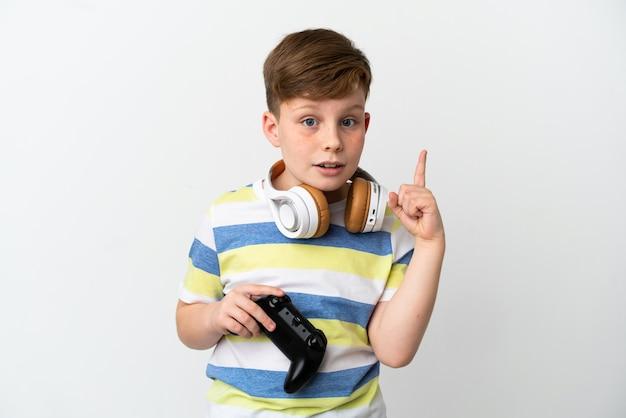 Mały rudy chłopiec trzymający konsolę do gier na białym tle, który zamierza zrealizować rozwiązanie, podnosząc palec w górę