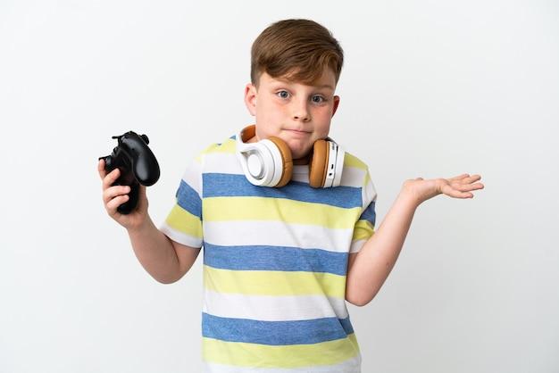Mały rudy chłopiec trzymający konsolę do gier na białym tle mający wątpliwości podczas podnoszenia rąk
