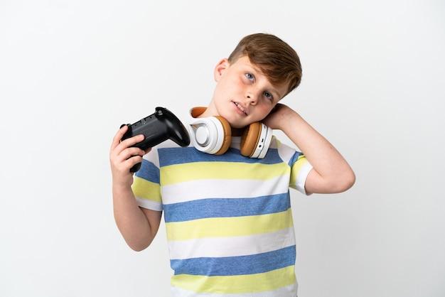 Mały rudy chłopiec trzymający konsolę do gier na białym tle mający wątpliwości