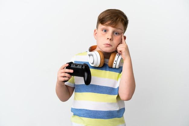 Mały rudy chłopiec trzymający konsolę do gier na białym tle myślący o pomyśle