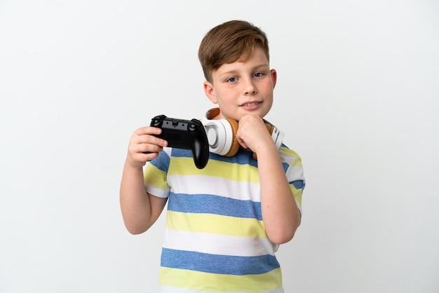 Mały rudy chłopiec trzymający konsolę do gier na białym tle, patrząc w bok i uśmiechnięty