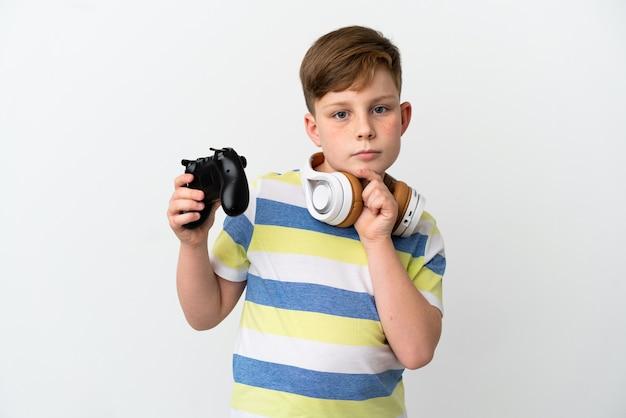Mały rudy chłopiec trzymający konsolę do gier na białym tle patrząc w górę podczas uśmiechania się
