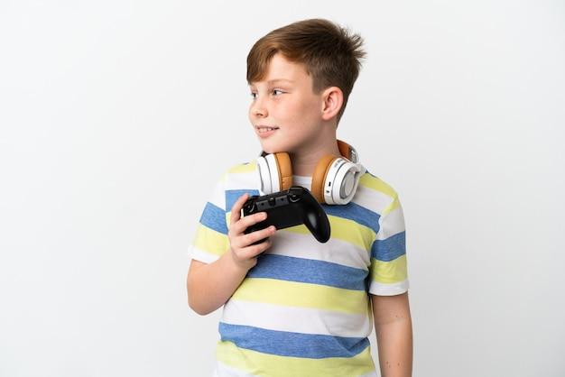 Mały rudy chłopiec trzymający konsolę do gier na białym tle patrząc z boku